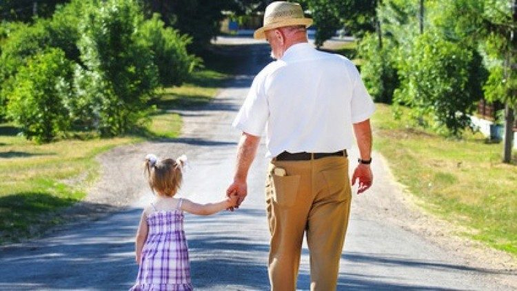 A young girl takes a walk with her grandfather