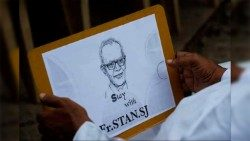 A man holds an image of Fr. Stan Swamy, SJ