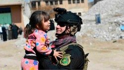 In Mosul, against a backdrop of rubble, a little girl looks at a soldier and smiles as he lifts her up