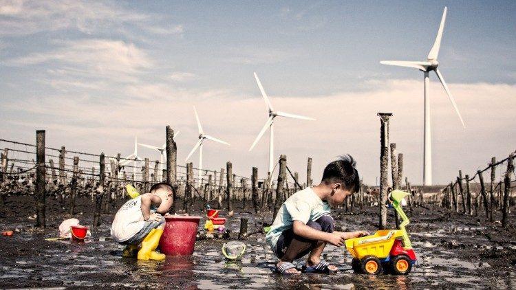 Children play near wind turbines