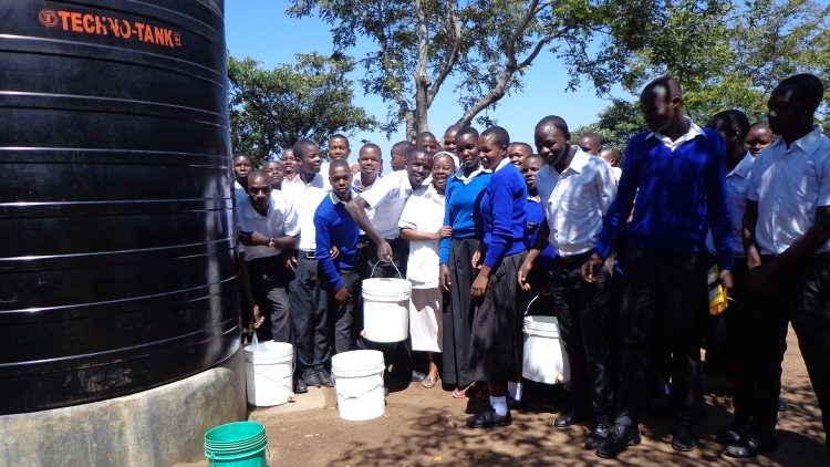 Sr. Bokamba with colleagues and students at one of the water project tanks in Mosanga, Tanzania