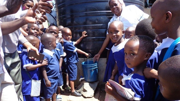 Sr. Bokamba with local schoolchildren at one of the water tanks